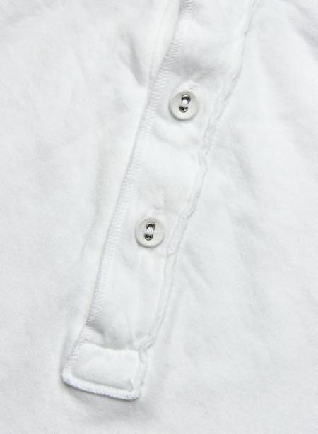 Un bon exemple de T-shirt col tunisien avec des boutons en tissu